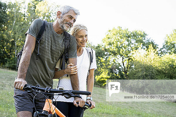 Smiling mature couple with bicycle standing in forest