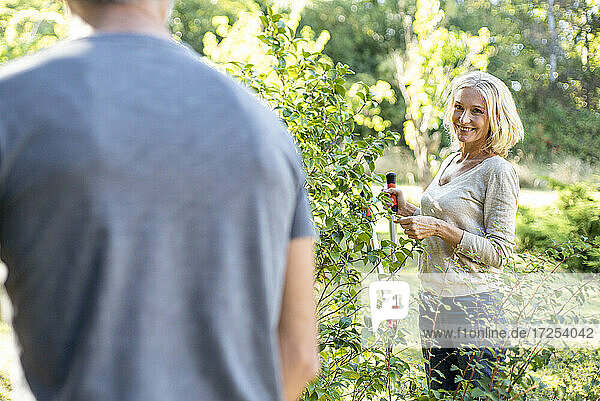 Smiling mature woman with secateurs looking at her husband in backyard