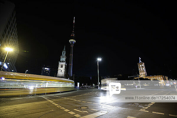 Low angle view of church and Fernsehturm Berlin with tram driving on street in foreground at night