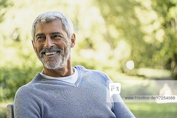 Smiling mature man sitting on chair in backyard