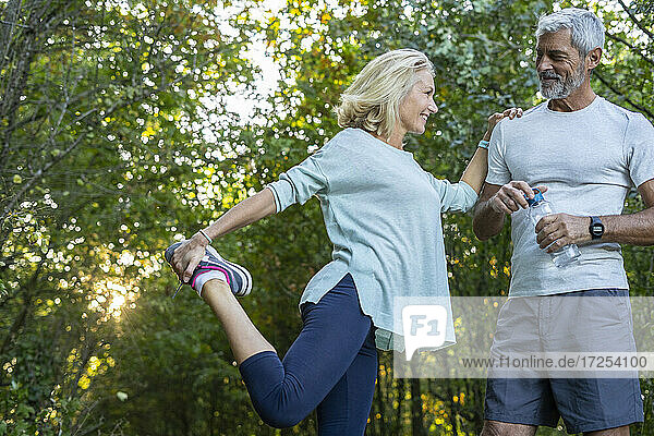 Low angle view of smiling mature couple looking at each other while exercising in forest