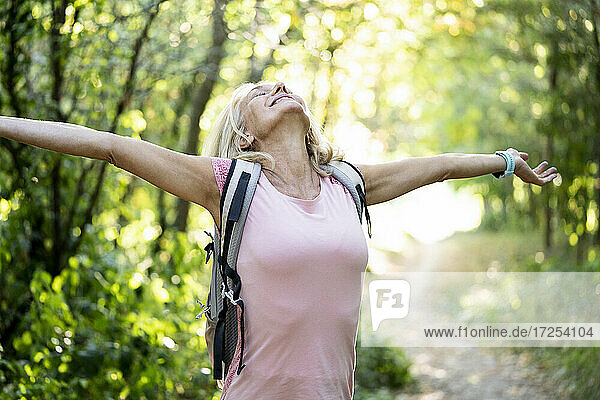 Smiling mature woman stretching arms while standing in forest