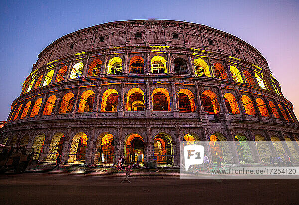 Low angle view of tourists walking on street outside Colosseum at dusk  Rome