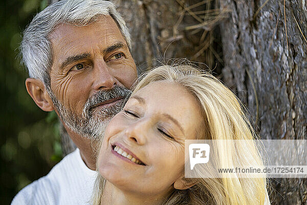 Close-up of smiling mature couple leaning on tree trunk