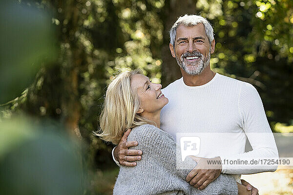 Smiling mature couple embracing each other in backyard