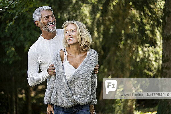 Smiling mature couple standing in backyards