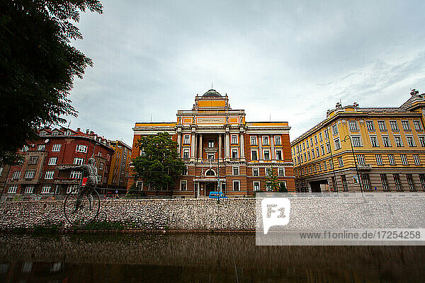 Low angle view of University of Sarajevo with Miljacka River in foreground