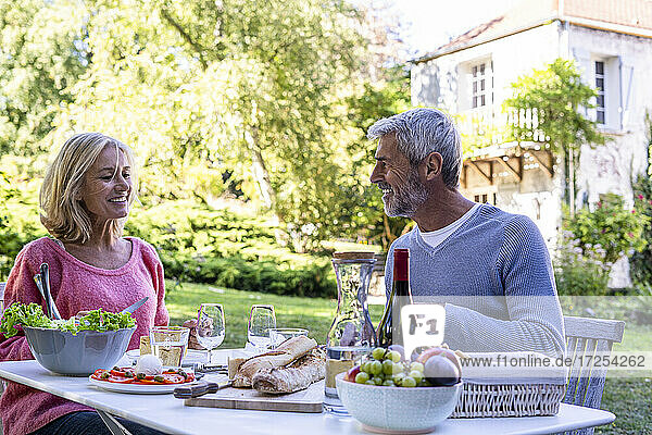 Smiling mature couple enjoying meal while sitting at table