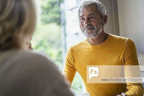 Smiling mature man looking at his wife at home