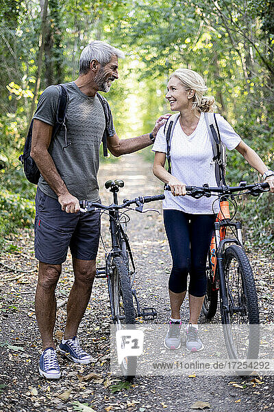 Smiling mature couple with bicycles walking on footpath in forest
