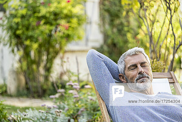 Mature man with eyes closed relaxing on deckchair