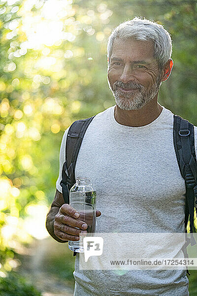 Portrait of smiling mature man holding water bottle in forest