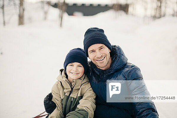 Portrait of cheerful father with arm around son during winter