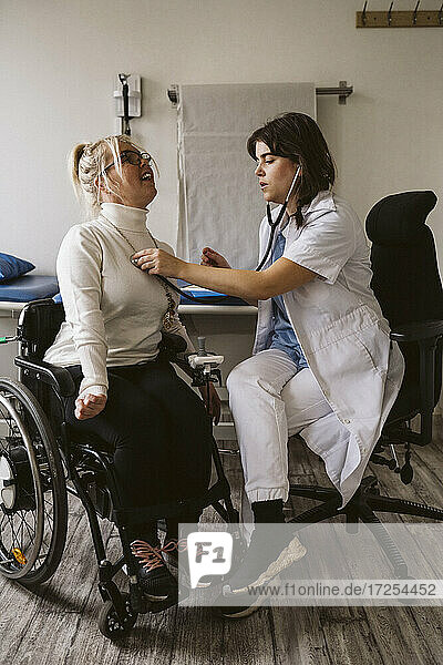 Full length of female healthcare worker examining disabled patient with stethoscope in medical clinic