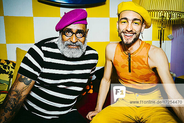 Lächelnder junger Mann mit älterem männlichen Freund  der eine Baskenmütze trägt  sitzt im Wohnzimmer