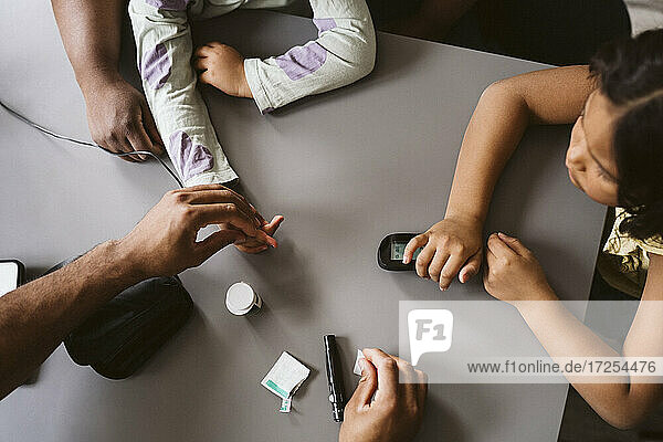 Male doctor doing sugar test of girl in medical clinic
