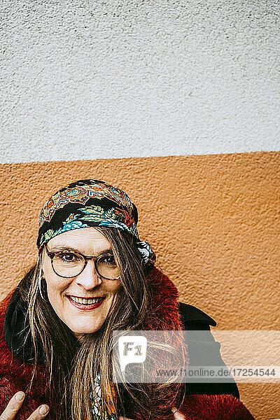 Portrait of smiling mature woman wearing fur coat against wall