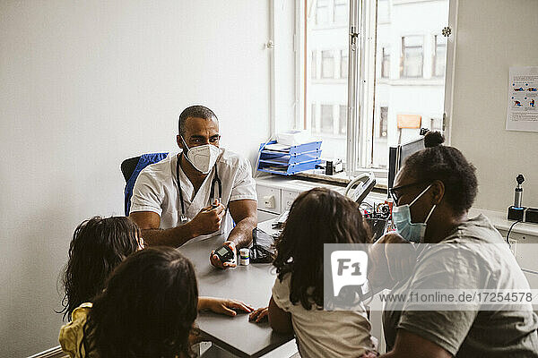 Male doctor talking with woman and girls sitting at desk during COVID-19