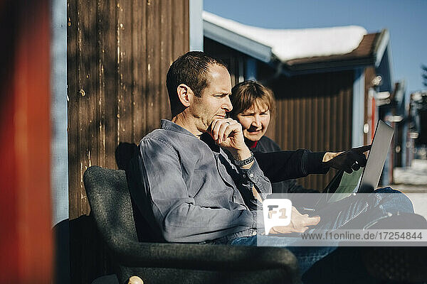 Female entrepreneur discussing over laptop with businessman while sitting against vacation home