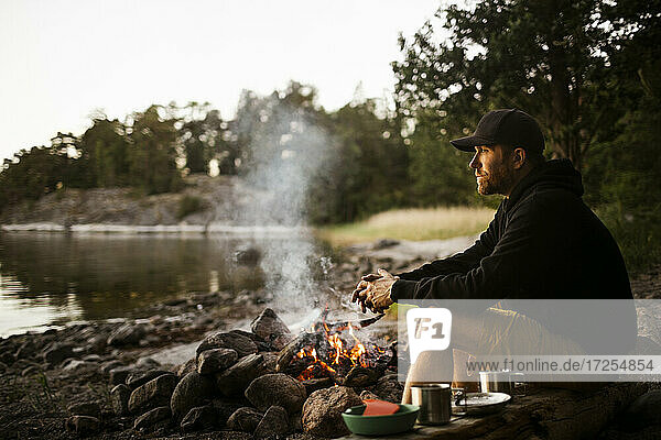 Side view of thoughtful man looking away while sitting by campfire at lakeshore