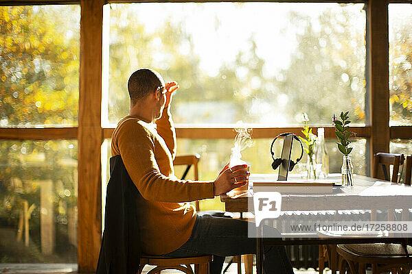 Geschäftsmann mit heißem Kaffee arbeiten am Tisch in sonnigen Herbst-Café