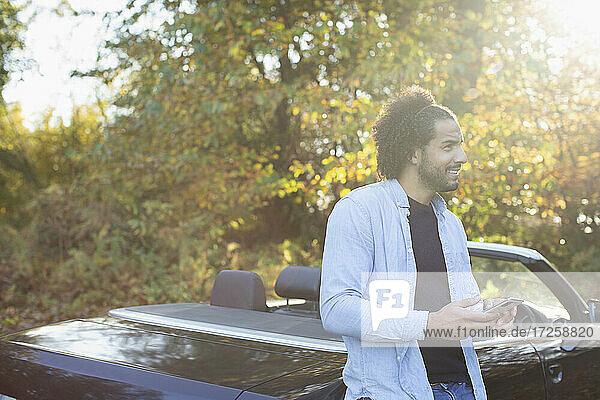 Junger Mann mit Smartphone am Cabrio im sonnigen Herbst Park