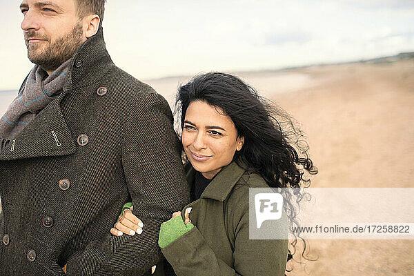 Glückliches Paar in Wintermänteln am Strand