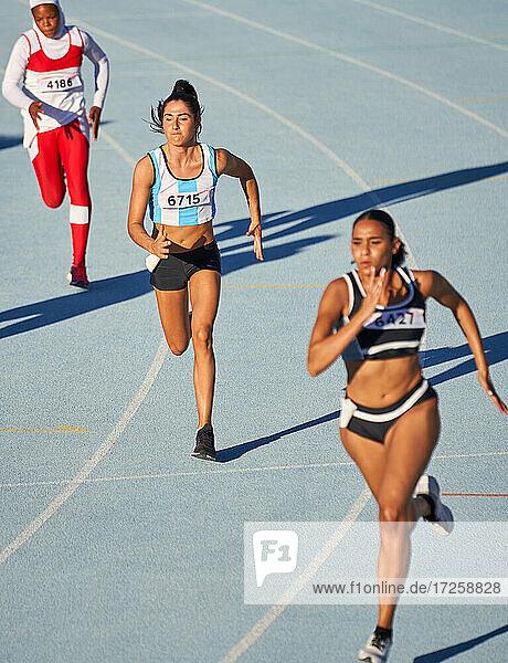 Leichtathletinnen beim Laufen auf der Bahn im Wettkampf