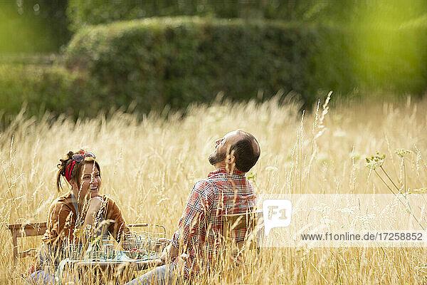 Glückliches Paar lachend am Tisch im Feld der sonnigen hohen Gras