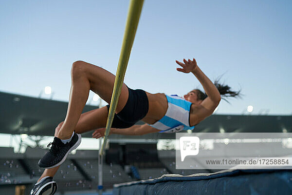Female track and field athlete high jumping over pole