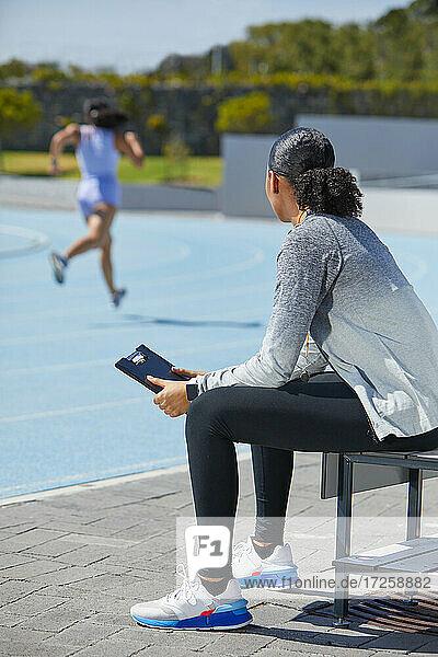 Weiblicher Leichtathletik-Trainer beobachtet Läufer auf sonniger Strecke