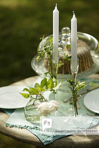 Kerzenständer und Rose auf Gartentisch mit Kuchen