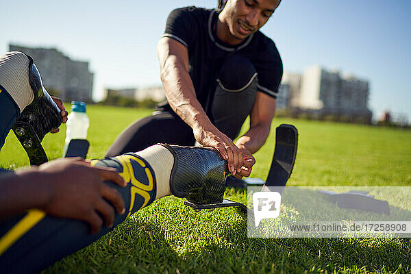 Trainer hilft amputiertem Athleten mit Laufblattprothese im Park
