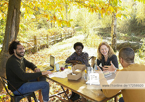 Happy business people meeting at table in sunny autumn park