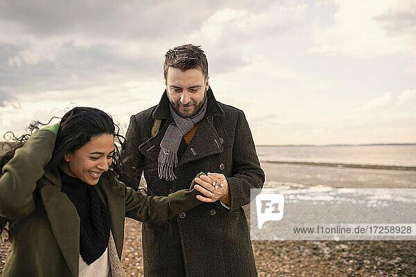 Glückliches Paar in Wintermänteln  die Hände haltend  am Strand spazierend