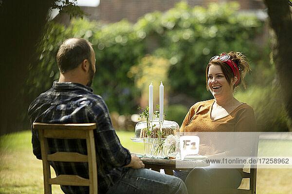 Happy couple enjoying cake at summer garden table