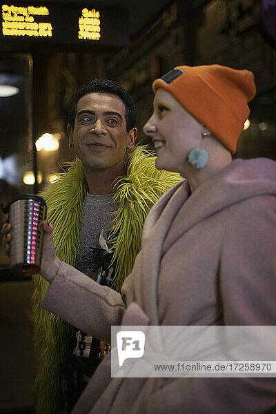 Glückliches Paar mit Kaffee warten an der Bushaltestelle in der Nacht