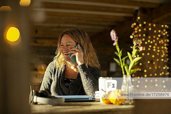 Glückliche Geschäftsfrau sprechen auf Smartphone arbeiten im Café