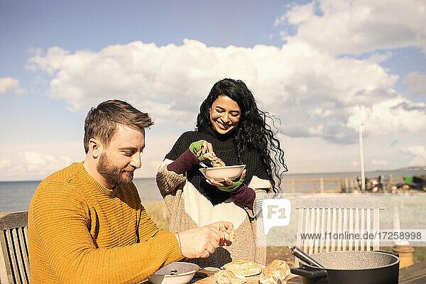 Paar genießt Chowder und Baguette auf der sonnigen Strandterrasse