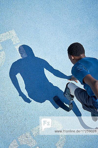 Junger männlicher amputierter Sprinter bereit auf sonniger blauer Sportbahn