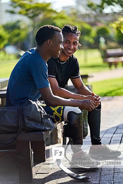 Männlicher amputierter Athlet und Trainer im Gespräch auf der Bank