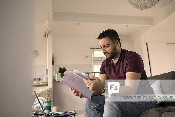 Mann mit Papierkram arbeiten von zu Hause am Laptop auf dem Sofa