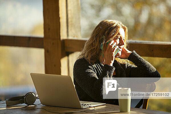 Geschäftsfrau im Gespräch auf Smartphone am Laptop in sonnigen Cafe