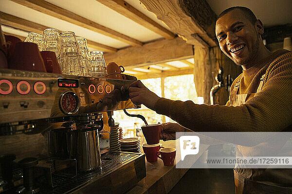 Porträt glücklich männlichen Barista Vorbereitung Kaffee im Café Espressomaschine