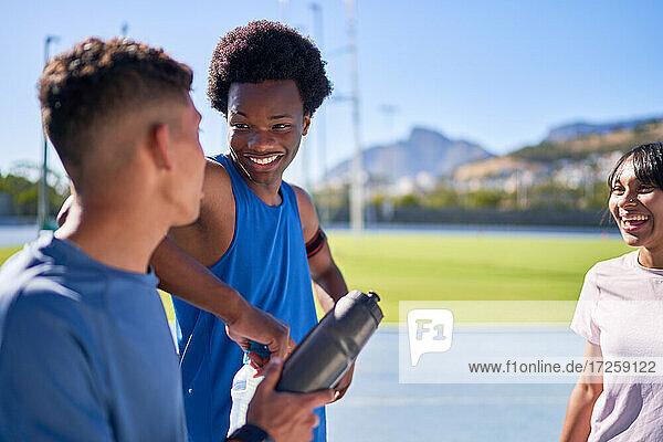 Glückliche junge Sportler im Gespräch auf der sonnigen Sportbahn