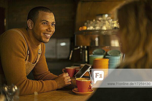 Glückliche männliche Barista  die Kundenbestellung am Café Tresen
