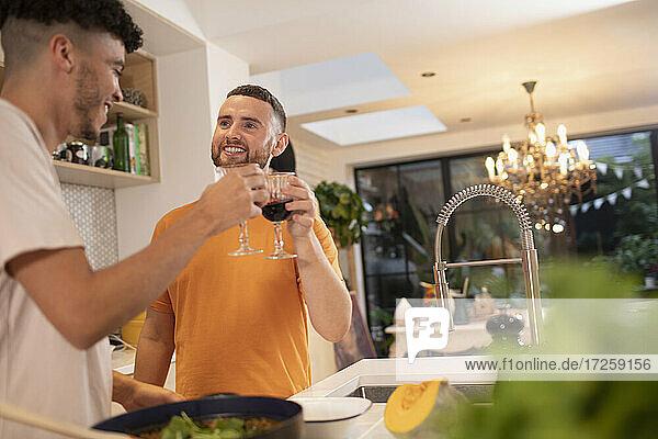 Glückliche Homosexuell männliches Paar trinken Wein und Kochen in der Küche