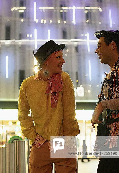Glückliches Paar im Gespräch unter modernen Stadt Gebäude in der Nacht
