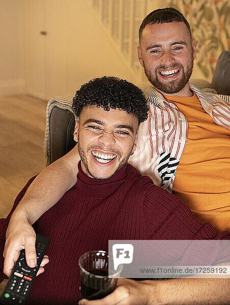 Glückliche Homosexuell männliches Paar Fernsehen und trinken Rotwein zu Hause