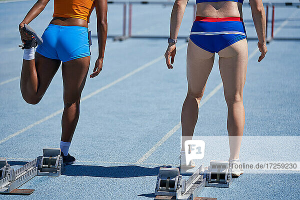 Female track and field athletes preparing at starting blocks